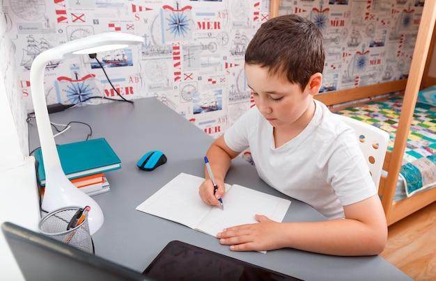 オンライン学習ホームスクーリングにデスクトップコンピューターを使用している少年 Premium写真