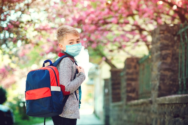 Школьник носить маску во время вспышки вируса короны. обратно в школу концепции. Premium Фотографии