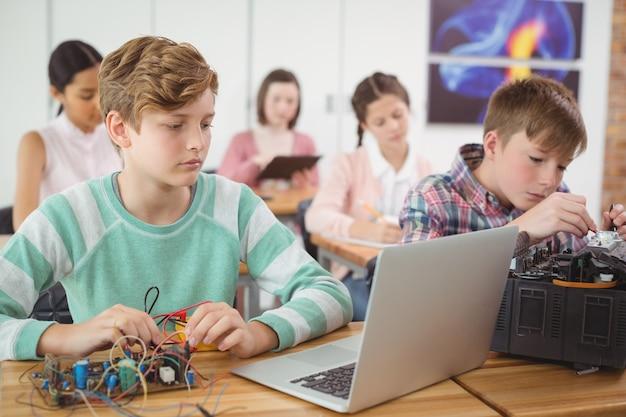 教室で電子プロジェクトに取り組んでいる男子生徒 Premium写真