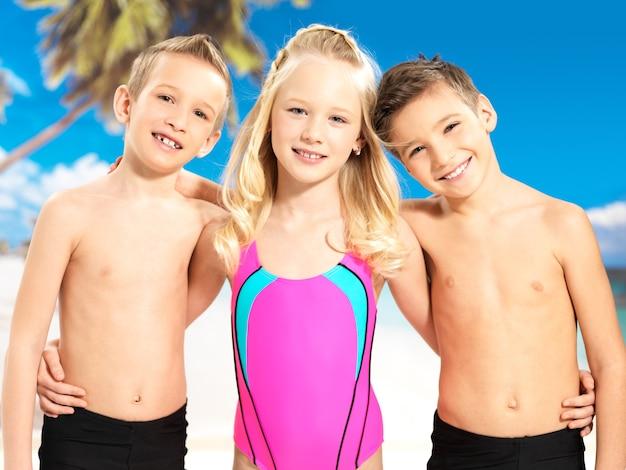 明るい色の水着で一緒に立っている学童の子供たち。 無料写真