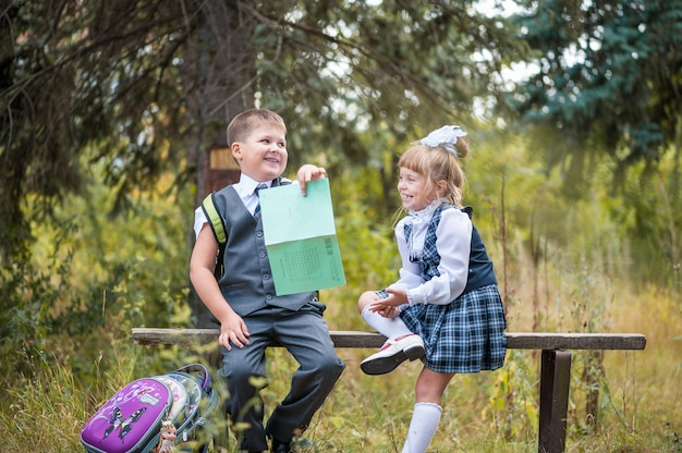 Schoolchildren sit on a bench with briefcases and notebooks after school. Premium Photo
