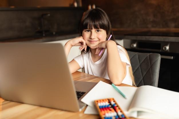 ノートパソコンでオンライン学習後の女子高生。女の子はビデオ通話で勉強し、家で宿題をします。遠隔教育 Premium写真