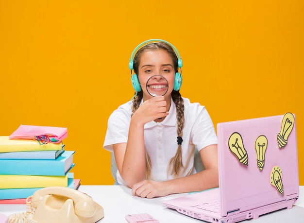 Schoolgirl on desk with laptop in memphis style Free Photo