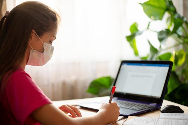 インターネット経由で自宅で学校のタスクを行う女子高生。コロナウイルスの検疫と遠隔学習 Premium写真