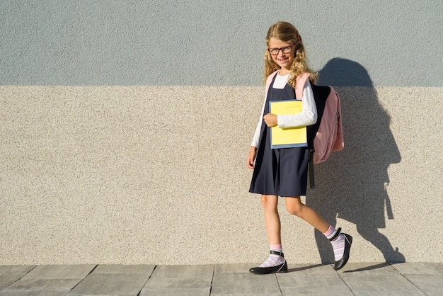 Schoolgirl of elementary school with notebooks in his hand Premium Photo