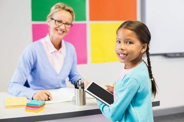 Schoolgirl holding digital tablet in classroom Premium Photo