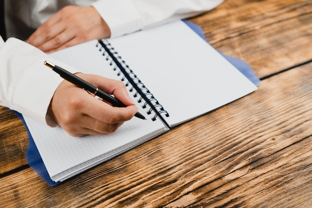 A schoolgirl is sitting at a table with a notebook and a pen. Premium Photo