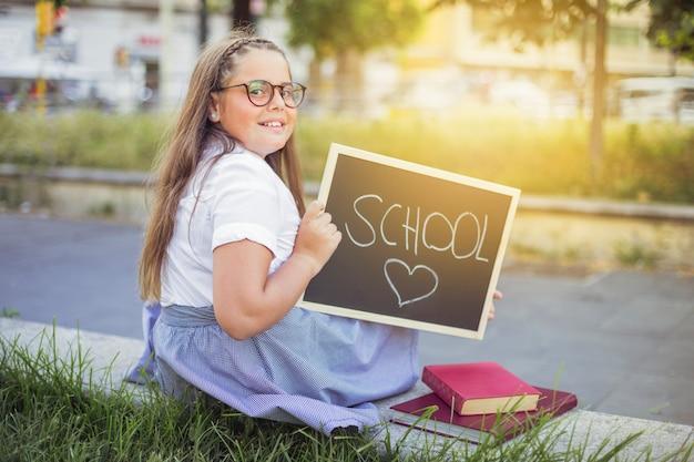 Schoolgirl in uniform with sign school love Free Photo