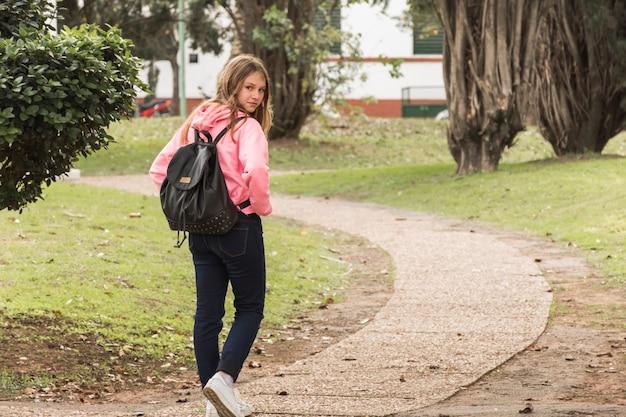 Schoolgirl walking in park Free Photo