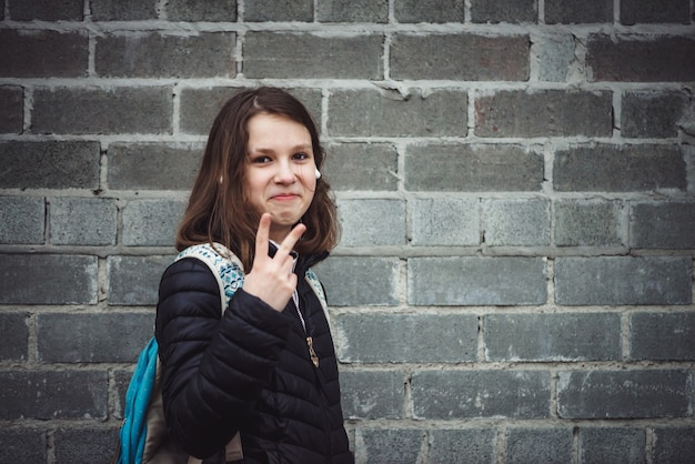 Школьница с рюкзаком стоит у серой кирпичной стены с искусственными эмоциями Premium Фотографии