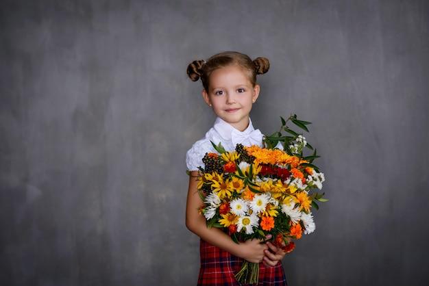 Schoolgirl with bouquet of flowers. school concept Premium Photo