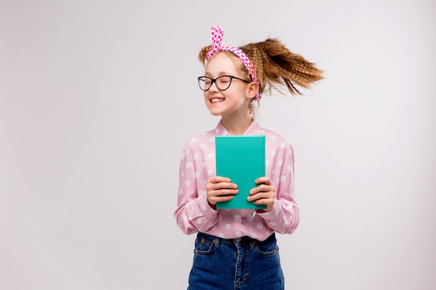 Schoolgirl with glasses with a book smiling Premium Photo