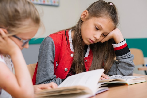 Schoolgirls sitting at desk reading Free Photo