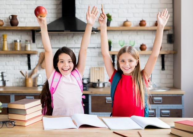 Schoolgirls with hands up standing in kitchen Free Photo