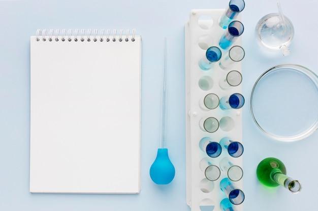 Elementi di scienza in laboratorio con blocco note vuoto Foto Gratuite