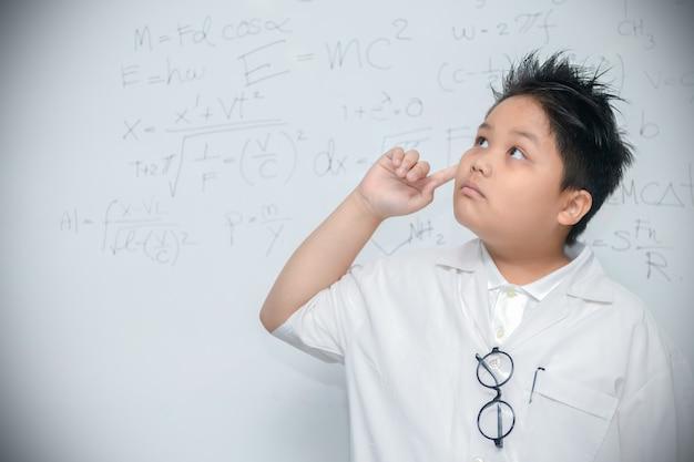 Ученый мальчик мышления на белом фоне Premium Фотографии