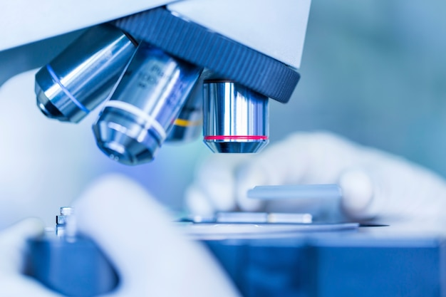 Scientist hands with microscope, examining samples, concept science and technology Premium Photo
