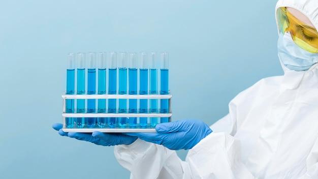Scienziato che tiene i prodotti chimici blu Foto Gratuite