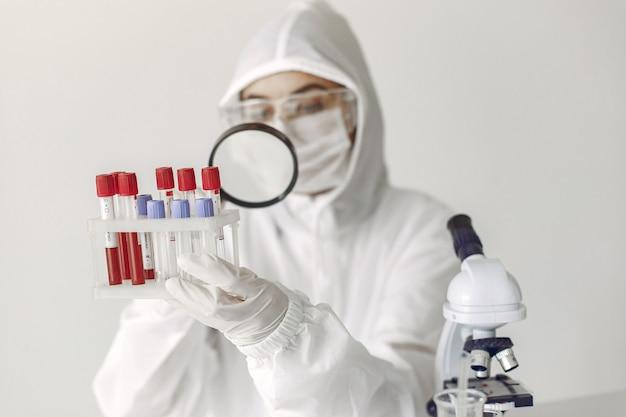 Ученый в спецодежде исследует образец коронавируса в лаборатории Бесплатные Фотографии