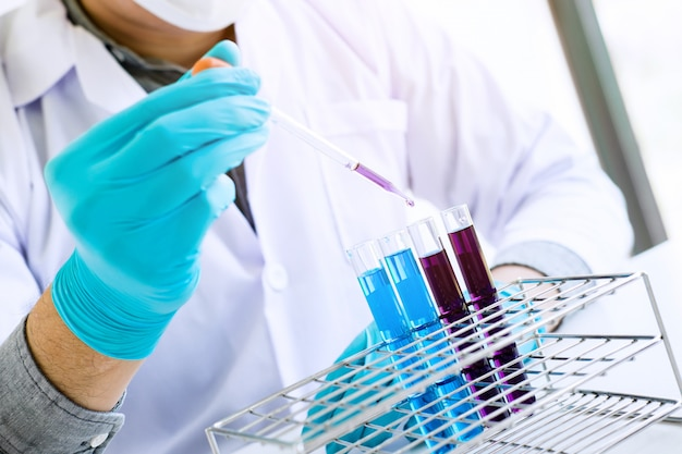 Scientist or medical in lab coat holding test tube with reagent with drop of color liquid Premium Photo