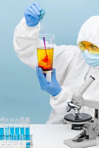 Scienziato che mescola diverse sostanze Foto Gratuite