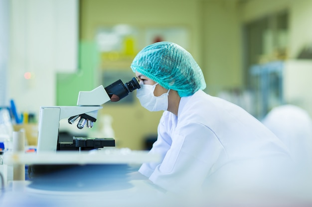 Scientist using a microscope in a laboratory, concept science and technology Premium Photo