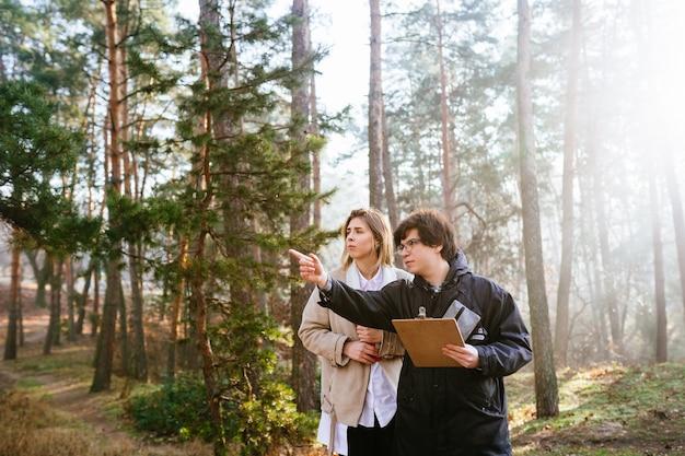 Ученые изучают виды растений и осматривают деревья в лесу. Бесплатные Фотографии