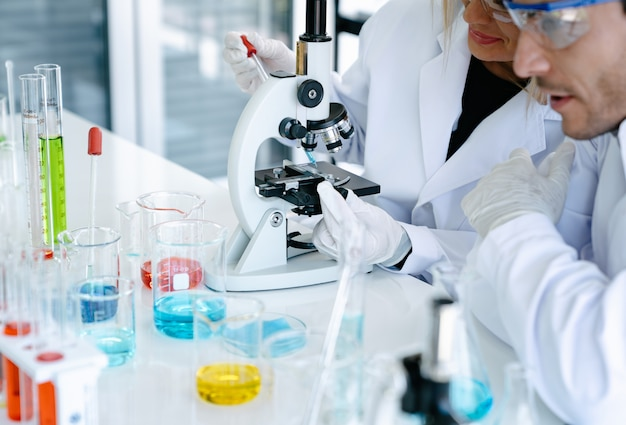 Scientists checking medical liquid with microscope while doing health care research in laboratory Premium Photo