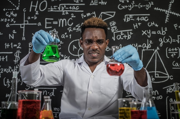 Scientists hold beakers with green and red chemicals and stressed faces Free Photo