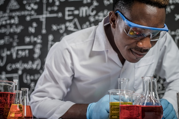 Scientists look at the chemicals in glass at the laboratory Free Photo