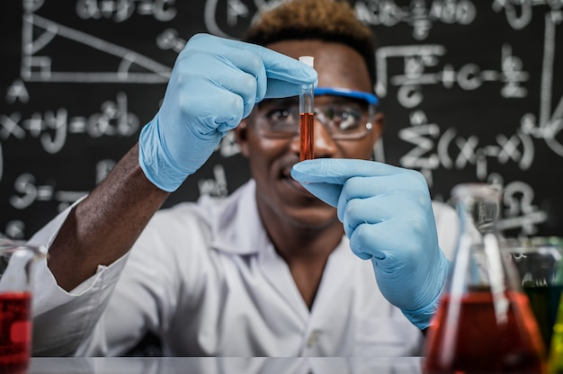 Scientists look at the orange chemicals in glass at the laboratory Free Photo