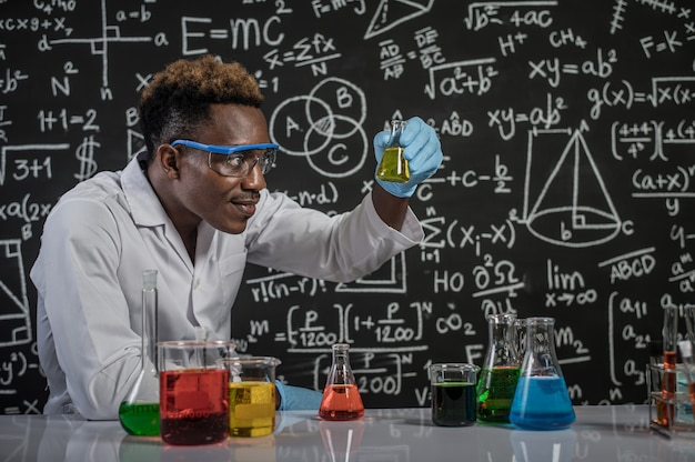 Scientists look at the yellow chemicals in glass at the laboratory Free Photo