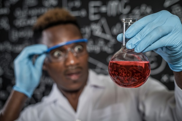 Scientists shocked by the red chemicals in glass at the laboratory Free Photo
