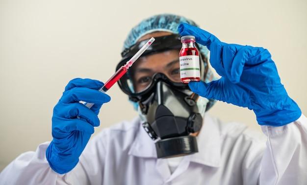 Scienziati che indossano maschere e guanti in possesso di una siringa con un vaccino per prevenire covid-19 Foto Gratuite