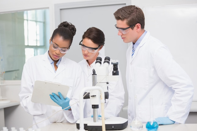 Scientists working with microscope and taking notes Premium Photo