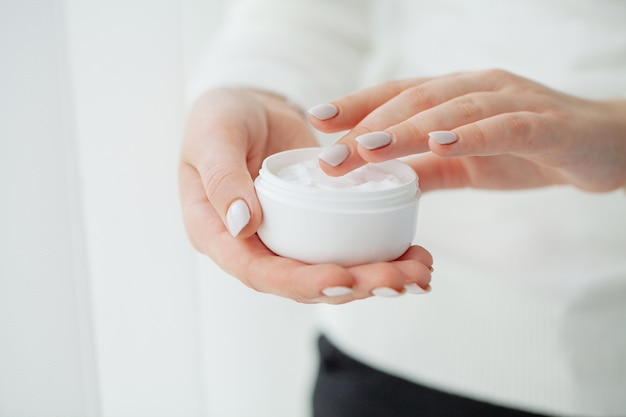 Scin care. beautiful woman hands with cream Premium Photo