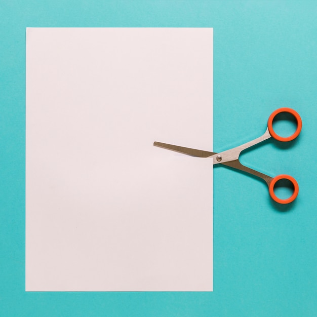 Scissors cutting paper on blue background Free Photo