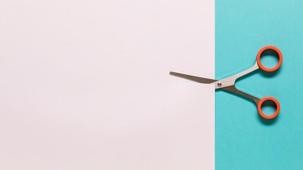 Scissors cutting white paper Free Photo