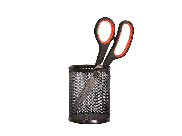 Ножницы с красной ручкой в черном металлическом держателе. изолировать Premium Фотографии
