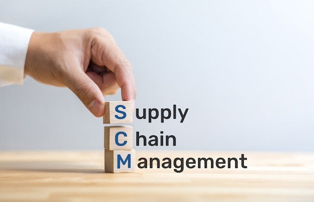 Scm text on wood box with male hand.business and  industry management