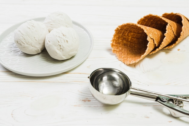 Scoop near plate with ice-cream and cones Free Photo