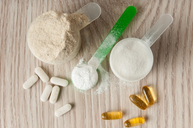 Scoop of protein, bcaa and creatine, omega3 in pills Premium Photo