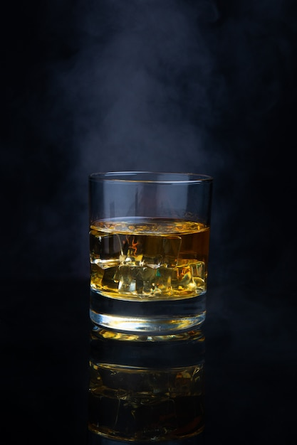 Scotch whiskey with ice and smoke Premium Photo
