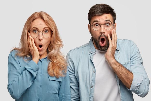 Поцарапанная эмоциональная семейная пара смотрит с удивлением, недоумевая Бесплатные Фотографии