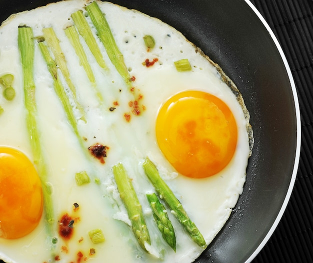 Scrambled eggs in a frying pan with asparagus Premium Photo