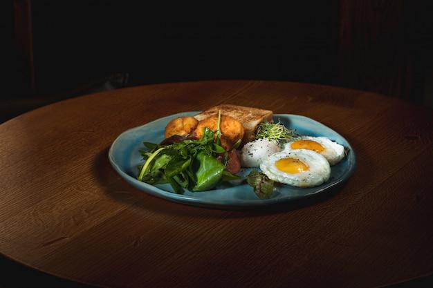 Uova strapazzate su carne con patate fritte e pane tostato Foto Gratuite