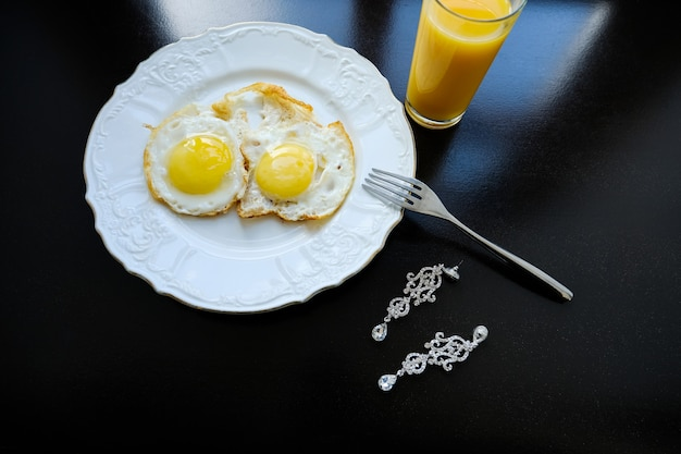 Scrambled eggs on a white plate, orange juice. next are the bride's earrings. Premium Photo