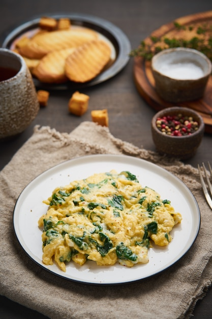 Scrambled eggs with spinach, cup of tea on dark brown Premium Photo