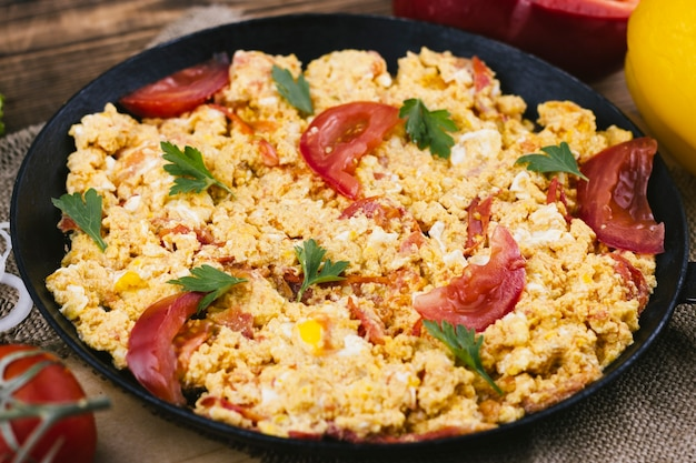 Scrambled eggs with tomatoes in a pan Free Photo