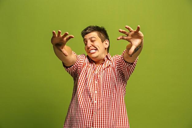 Urla, odio, rabbia. piangere uomo arrabbiato emotivo che grida su sfondo verde studio. emotivo, giovane faccia. ritratto maschile a mezzo busto. Foto Gratuite